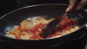 Den högg av lökar, moroten och tomaten stekte i grönsakolja i pannan Närbild som överst tillfogar tomaten av pannan lager videofilmer