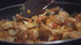 Den högg av lökar, moroten och tomaten stekte i grönsakolja i pannan Närbild som överst tillfogar höna av pannan lager videofilmer