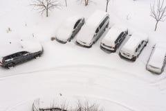 Den högstämda sikten av snö täckte bilar i parkeringsplats Royaltyfria Foton