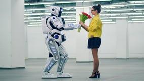 Den högväxta roboten ger blommor till en kvinna i en tom korridor arkivfilmer