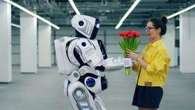 Den högväxta roboten ger blommor till en upphetsad flicka arkivfilmer