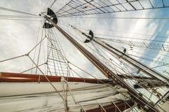 Den högväxta skeppmasten och seglar Arkivfoto