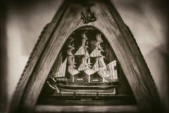 Den högväxta skeppmodellen i den triangulära träramen, ankaret, repet som isolerades på suddig bakgrund, bleknade i sepiastilfoto royaltyfri foto