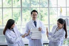 Den h?ga asiatiska forskaren har att tilldela nytt jobb till studenter i laboratorium arkivfoto