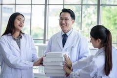 Den h?ga asiatiska forskaren har att tilldela nytt jobb till studenter i laboratorium royaltyfri bild