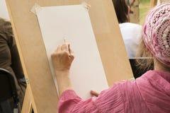 Den h?ga kvinnan drar med blyertspennan p? konststudion f?r ?ldre folk arkivfoto