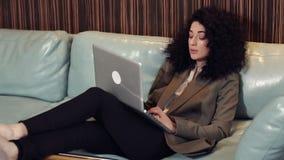Den h?rliga brunettmodellen, med lockigt h?r, sitter med en b?rbar dator p? soffan arkivfilmer