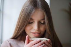 Den h?rliga flickan dricker kaffe och ler, medan sitta p? kaf?t royaltyfria bilder