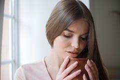 Den h?rliga flickan dricker kaffe och ler, medan sitta p? kaf?t arkivbilder