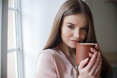 Den h?rliga flickan dricker kaffe och ler, medan sitta p? kaf?t royaltyfri fotografi