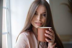 Den h?rliga flickan dricker kaffe och ler, medan sitta p? kaf?t arkivbild