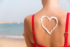 Den h?rliga flickan i r?d baddr?kt har sunblock i form av hj?rta baktill p? stranden arkivbilder