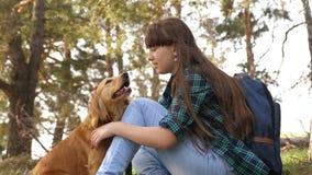 Den h?rliga flickan reser med husdjuret turist- flicka i skog p? stopp med en hund husmor spelar med att jaga hund husmor stock video