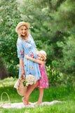 Den h?rliga gravida flickan i en sugr?rhatt st?r med en bukett av sommarblommor bredvid hennes lilla dotter och kramar i arkivfoto