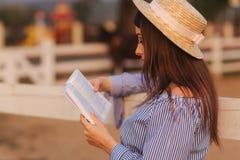 Den h?rliga gravida kvinnan l?ste boken p? lantg?rden Hon st?r vid fancen och ser in till boken relax royaltyfria foton