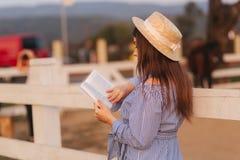 Den h?rliga gravida kvinnan l?ste boken p? lantg?rden Hon st?r vid fancen och ser in till boken relax fotografering för bildbyråer