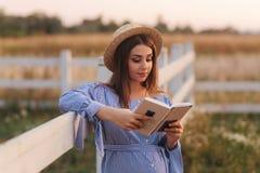 Den h?rliga gravida kvinnan l?ste boken p? lantg?rden Hon st?r vid fancen och ser in till boken relax royaltyfri bild