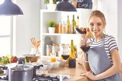 Den h?rliga kvinnan i k?k dricker r?tt vin royaltyfri bild