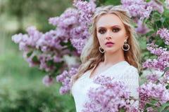 Den h?rliga kvinnan som tycker om lilatr?dg?rden, den unga kvinnan med blommor i gr?splan, parkerar arkivbild