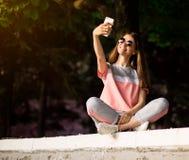 Den h?rliga stads- kvinnan i solglas?gon g?r selfiest?enden utomhus- i sommardag royaltyfri foto