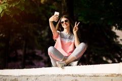 Den h?rliga stads- kvinnan i solglas?gon g?r selfiest?enden utomhus- i sommardag royaltyfri bild