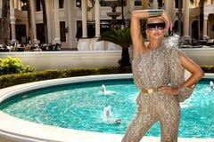 Den h?rliga trendiga unga kvinnan som poserar i, parkerar, solglas?gon, jumpsuiten, h?ga h?l, blont h?r Modesommarfoto brigham arkivbild