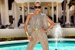 Den h?rliga trendiga unga kvinnan som poserar i, parkerar, solglas?gon, jumpsuiten, h?ga h?l, blont h?r Modesommarfoto brigham arkivfoton