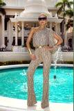 Den h?rliga trendiga unga kvinnan som poserar i, parkerar, solglas?gon, jumpsuiten, h?ga h?l, blont h?r Modesommarfoto brigham fotografering för bildbyråer