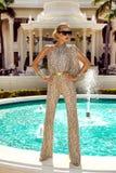 Den h?rliga trendiga unga kvinnan som poserar i, parkerar, solglas?gon, jumpsuiten, h?ga h?l, blont h?r Modesommarfoto brigham royaltyfria foton