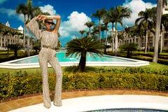 Den h?rliga trendiga unga kvinnan som poserar i, parkerar, solglas?gon, jumpsuiten, h?ga h?l, blont h?r Modesommarfoto brigham arkivfoto