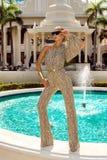 Den h?rliga trendiga unga kvinnan som poserar i, parkerar, solglas?gon, jumpsuiten, h?ga h?l, blont h?r Modesommarfoto brigham arkivbilder