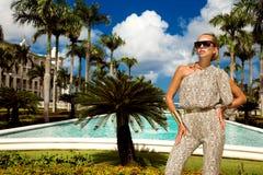 Den h?rliga trendiga unga kvinnan som poserar i, parkerar, solglas?gon, jumpsuiten, h?ga h?l, blont h?r Modesommarfoto brigham royaltyfria bilder