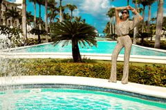 Den h?rliga trendiga unga kvinnan som poserar i, parkerar, solglas?gon, jumpsuiten, h?ga h?l, blont h?r Modesommarfoto brigham royaltyfri bild