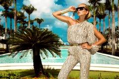 Den h?rliga trendiga unga kvinnan som poserar i, parkerar, solglas?gon, jumpsuiten, h?ga h?l, blont h?r Modesommarfoto brigham royaltyfri foto