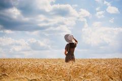 Den h?rliga unga kvinnan med brunt h?r den b?rande roskl?nningen och hatten som tycker om utomhus att se till horizonten p? perfe arkivfoto