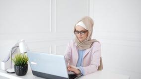 Den h?rliga unga muslim kvinnan arbetar p? b?rbara datorn p? hennes arbetsplats lager videofilmer