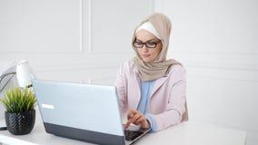 Den h?rliga unga muslim kvinnan arbetar p? b?rbara datorn p? hennes arbetsplats arkivfilmer