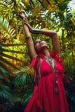 Den h?rliga unga trendiga kvinnan med utg?r och stilfull bohotillbeh?r som poserar p? naturlig tropisk bakgrund fotografering för bildbyråer