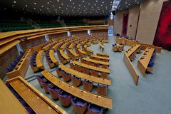 Wide view of interior of the empty plenary hall of the House of Representatives with centre the place where the ministers sit royalty free stock photo