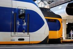 Den Hague, die Niederlande, am 15. Februar 2019: Züge, ein Sprinter und Intercityzur Abfahrt neben einander warten stockbilder