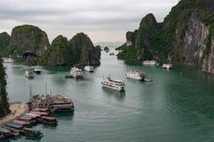 Den Halong fjärden med kryssningskepp och fartyg nära förvånar grottan Royaltyfri Foto