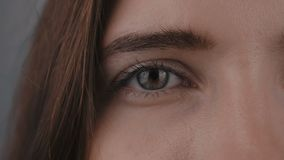 Den halva framsidan av ögat för ` s för den unga kvinnan, stirrar hon in i kamera Slutet av ` s för den unga kvinnan synar upp lager videofilmer
