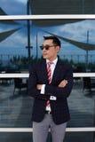 Den halva längdståenden av kläder för ceo för den lyckade mannen som iklädd företags står med korsade armar, near kontorsbyggnad, arkivbild