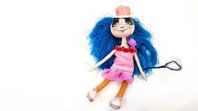 Den handgjorda dockan göras av ett material med stora ögon i rosa färgklänning och hatt, med blått hår av garn på en vit bakgrund fotografering för bildbyråer