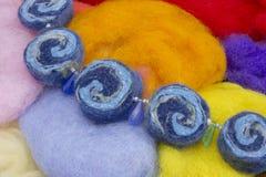Den handgjorda halsbandet som göras av ljus färgrik ull för den torra naturliga merinoen, pryder med pärlor, klädde med filt tork Arkivbilder
