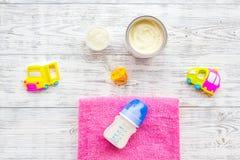 Den handgjorda leksaker för nyfött behandla som ett barn rattle Matningsflaskan med mjölkar Bästa sikt för vit träbakgrund arkivbild