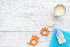 Den handgjorda leksaker för nyfött behandla som ett barn rattle Matningsflaskan med mjölkar Vit trämodell för bästa sikt för bakg royaltyfri fotografi