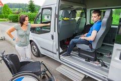 Den handikappade pojken väljs upp av skolbussen royaltyfri foto