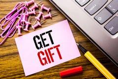 Den handskrivna textvisningen får gåvan Affärsidé för den fria Shoping kupongen som är skriftlig på rosa klibbigt anmärkningspapp Royaltyfri Foto