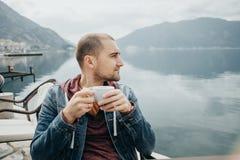 Den Handsom mannen dricker kaffe i ett kafé vid havet, Montenegro Arkivbild